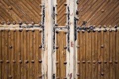 Alte braune Holztür mit metallischen Verzierungen auf einer hölzernen Wand Stockfotos