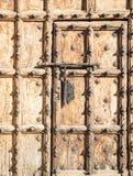 Alte braune Holztür mit metallischen Verzierungen und einem großen Bolzen Lizenzfreie Stockfotografie
