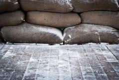 Alte braune Sandsäcke auf Schnee deckten hölzernen Boden ab Lizenzfreie Stockfotografie
