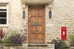 Alte braune Türen, roter Briefkasten in einem Steinhaus Stockfoto