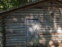 Alte braune und graue Bauernhofhalle mit verrostetem Rad auf der äußeren Wand im Wald lizenzfreies stockfoto