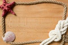 Alte Bretter mit dem Seilrahmen verziert durch Marineknoten und Muschel Stockbild