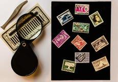 Alte Briefmarken aus unterschiedlichen Ländern, Vergrößerungsglas und tweez stockfotos