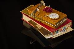 Alte Buchstaben, die Gläser, getrocknet stiegen, Taschenuhr alle auf einem schwarzen Hintergrund mit Leerstelle Lizenzfreies Stockbild
