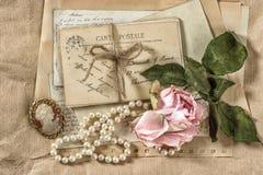 Alte Buchstaben, Postkarten, rosafarbene Blume und Weinlesesachen Lizenzfreie Stockfotos
