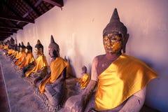 Alte Buddha-Statue, die entlang der Wand sitzt Stockbilder