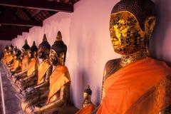 Alte Buddha-Statue, die entlang der Wand sitzt Stockbild