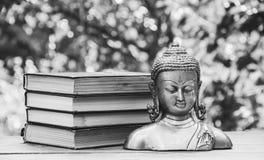 Alte Buddha-Statue und ein Stapel Bücher Religion und Kultur Stockfotografie