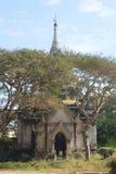 Alte buddhistische Pagode unter Bäumen an einem sonnigen Tag Bagan, Birma Lizenzfreies Stockfoto