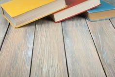 Alte bunte Bücher auf hölzernem Schreibtisch Zurück zu Schule Scheren und Bleistifte auf dem Hintergrund des Kraftpapiers Lizenzfreies Stockfoto