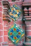 Alte bunte Endstücke auf der Wand der roten Backsteine der Offenbarungskirche Stockfoto