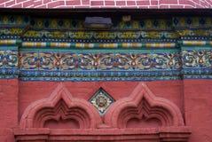 Alte bunte Endstücke auf der Wand der roten Backsteine der Offenbarungskirche Lizenzfreie Stockfotografie
