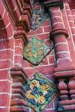 Alte bunte Endstücke auf der Wand der roten Backsteine der Offenbarungskirche Stockfotos