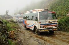Alte Busse auf sehr falscher schlammiger Straße, Nepal Stockbilder