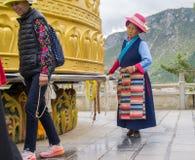 Alte Chinesin an einem Gebetsrad stockfotografie