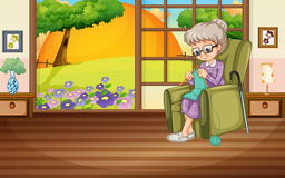 Alte Dame, die auf dem Lehnsessel strickt Lizenzfreies Stockfoto
