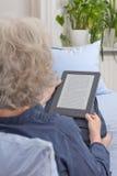 Alte Dame, die digitales Buch liest Lizenzfreie Stockfotografie