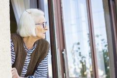 Alte Dame, die draußen durch ihr Fenster schaut Stockbild