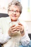 alte Dame, die ein Gebräu von Kräutern trinkt Stockfotografie