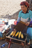 Alte Dame, die gegrillten Mais zubereitet stockbild