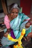 Alte Dame, die Girlande von Blumen verkauft. Goa, Indien. Lizenzfreie Stockfotografie