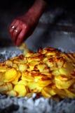 Alte Dame, die Ofenkartoffeln mit Zwiebeln zubereitet Lizenzfreie Stockfotos