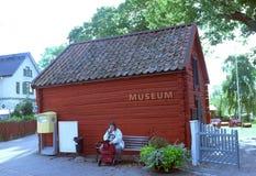 Alte Dame, die vor einem kleinen Museum sitzt Stockfotos
