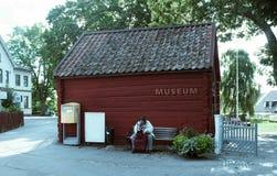 Alte Dame, die vor einem kleinen Museum sitzt Stockfotografie