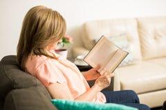 Alte Dame, die zu Hause ein Buch liest Stockfotografie