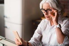 Alte Dame ist besorgt, neue Mitteilung an ihrem Telefon empfangend Stockbilder