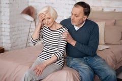 Alte Dame mit den Kopfschmerzen, die nahe ihrem Ehemann sitzen Lizenzfreies Stockfoto