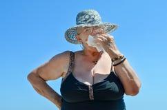 Alte Dame mit Hut Donut essend Stockfotografie