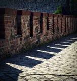 Alte defensive Backsteinmauer mit Schatten Stockfoto