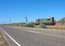 Alte Diesellokomotive, die entlang die Straße sich bewegt Stockfotografie