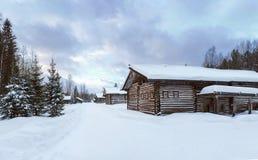 Alte Dorf-Blockhäuser im Museum kleines Karelians nahe Arkhangelsk, Russland Wintersonnenuntergangzeit Lizenzfreies Stockbild