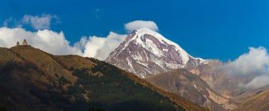 Alte Dreifaltigkeitskirche und ein Schnee bedeckten Berg von Kazbegi mit einer Kappe Lizenzfreies Stockbild