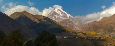 Alte Dreifaltigkeitskirche und ein Schnee bedeckten Berg von Kazbegi mit einer Kappe Lizenzfreie Stockfotografie