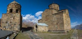 Alte Dreifaltigkeitskirche und ein Schnee bedeckten Berg von Kazbegi mit einer Kappe Lizenzfreies Stockfoto