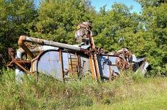Alte Dreschmaschine im langen Gras Stockfotos