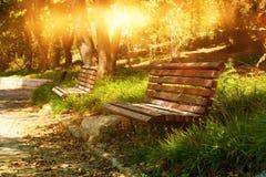 Alte einsame Bank im ruhigen Park am Sonnenunterganglicht Lizenzfreie Stockfotos