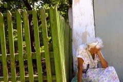 Alte einsame Frau, die auf der Straße in Ukraine sitzt Stockfotografie