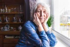 Alte einsame Frau, die nahe dem Fenster in seinem Haus sitzt stockfoto