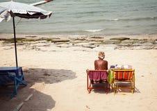 Alte, einsame, traurige Frau am schmutzigen, unordentlichen, sonnigen Strand Unglückliche, schlechte, langweilige Urlaubsreise zu Lizenzfreies Stockfoto