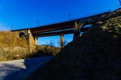 Alte Eisenbahnbrücke benutzt in den Bergen Ist ein grünes Feld voll der Weizenanlagen stockbild