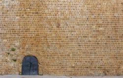 Alte Eisentür in der enormen alten Wand Stockbilder