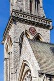 Alte englische Kirche der Uhr im Frühjahr Stockfotografie