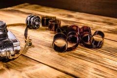 Alte Entfernungsmesserkamera und -filme auf Holztisch Lizenzfreies Stockfoto