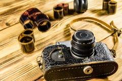 Alte Entfernungsmesserkamera und -filme auf Holztisch Stockfotos