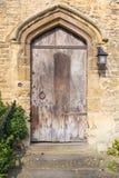 Alte europäische Holztür auf starker Steinwand Lizenzfreie Stockbilder