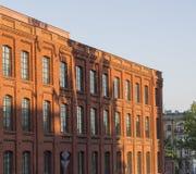 Alte Fabrik des roten Backsteins in Lodz im Abendlicht mit BAC des blauen Himmels Lizenzfreie Stockfotografie